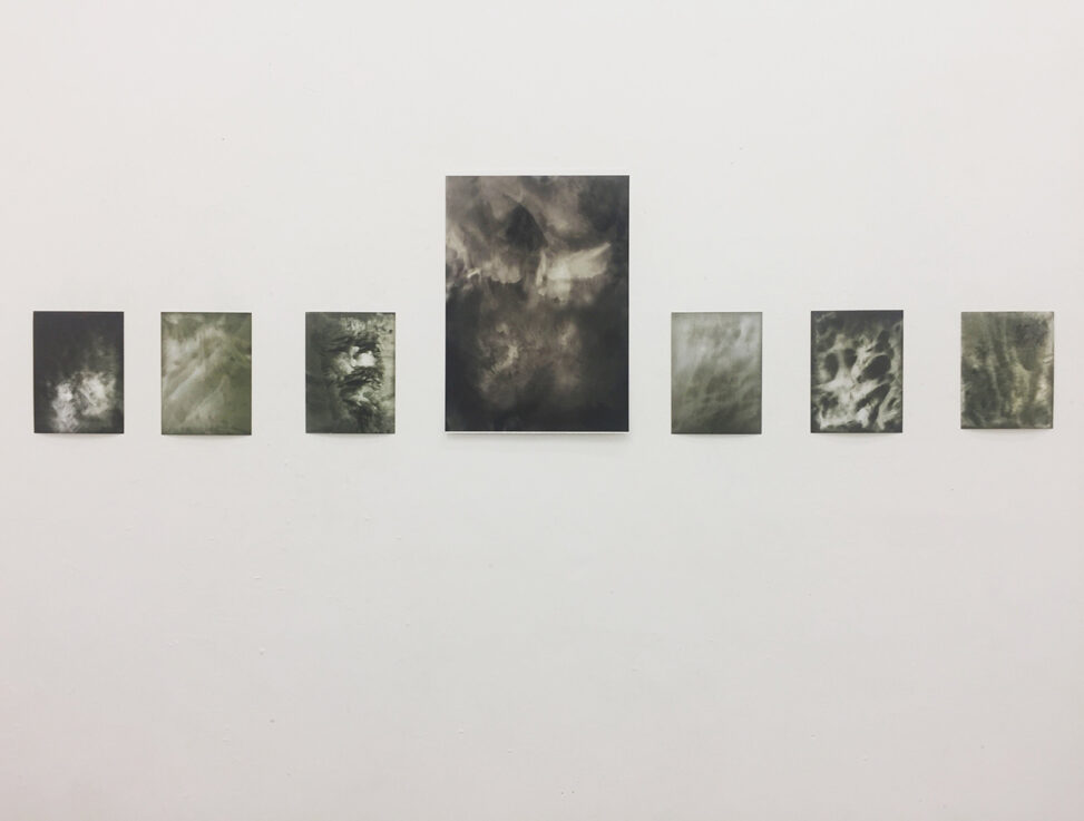 Photograph of a gallery wall with 7 black and white images on it.
